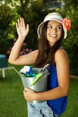 Attractive gardening girl waving