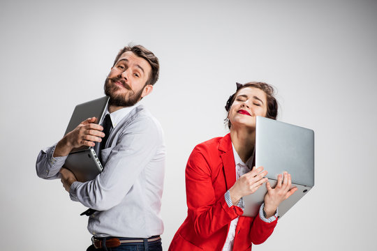 The young businessman and businesswoman with laptops on gray background
