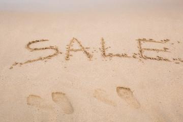Summer sale handwritten in sand on a beach