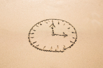 Time concept - Picture of a clock face on sandy beach.