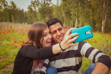 Couple taking selfie picture with their mobile phone in field of