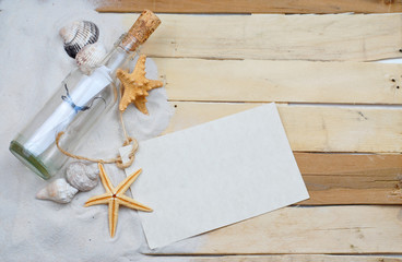 Summertime image with beachy theme of clean white sand scattered on boardwalk planks with starfish, seashells and a message in a bottle making a left side border with blank message tag.