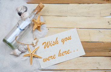 Summertime image with beachy theme of clean white sand scattered on boardwalk planks with starfish, seashells and a message in a bottle making a left side border with message tag.