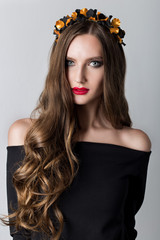 beautiful cute skinny girl with long hair with a wreath on his head and bright make-up in elegant black dress with bare shoulders in the studio
