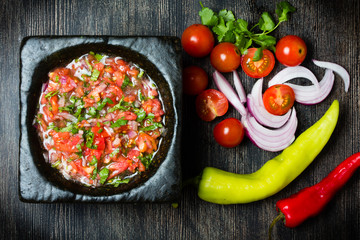 Tomato sauce salsa and ingredients dark stone background.