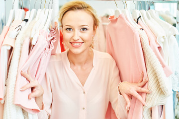 Portrait of a smiling girl among the coat racks in store with clothes