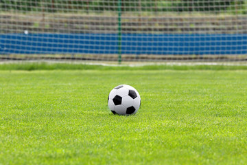 Soccer ball on football green field with space for text