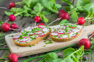 Bread with Curd Cheese, Radishes and Chive on Wooden Board on ol