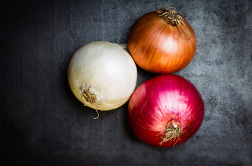 Different colorful onion on black background