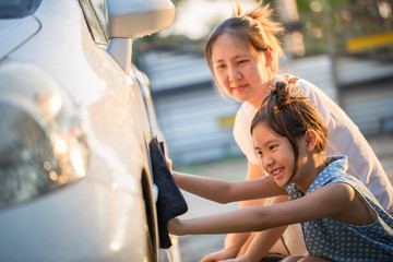 Happy Asian girl helping her mother washs car at home