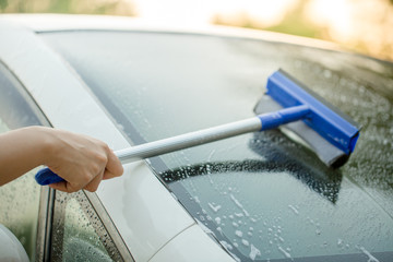 People cleaning car glass using cleaning brush