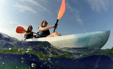 women smiling in blue kayak on tropical ocean