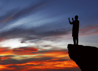 Silhouette of muslim man standing on the top of cliff
