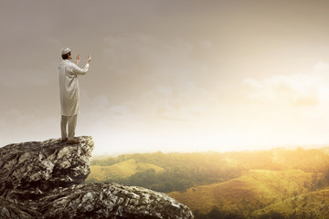 Image of muslim man standing on the top of cliff
