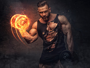 Portrait of bodybuilder with burning dumbbell.
