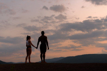 Silhouettes of athletic gymnastic couple watching the sunrise together. Beauty and perfection of human's body