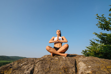 Portrait of sexy young athletic woman with muscular body practicing yoga on the rock. Blue sky background