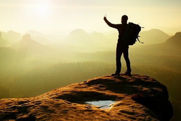 Strong hiker taking photo with smartphone, mountain peak