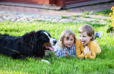 children lying on the grass with bernese mountain dog
