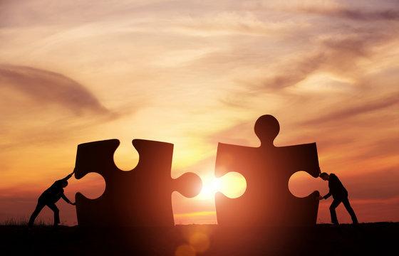 Teamwork concept. Two businessman connecting puzzle pieces