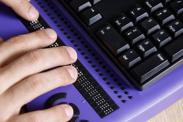 Blind person using computer with braille computer display