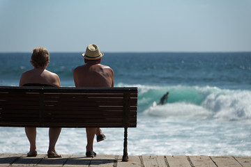 Elderly couple sitting on a bench overlooking the sea,background surfer on a wave