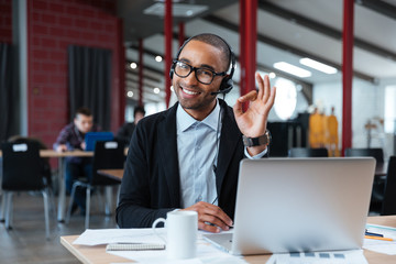 Businessman wearing headphones and showing okay sign
