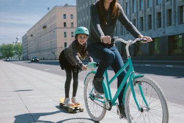 Mother and daughter ride a scooter and bicycle together