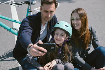 Happy Parents and Children take photo with a Bike, Skateboard an