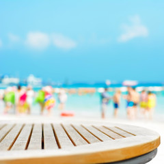 Round table top on blur beach background with people in colorful clothes