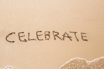 celebrate word handwritten on a sand of beach