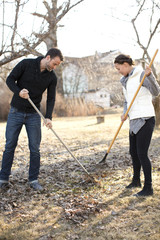 Couple raking leaves in garden, Stockholm, Sweden