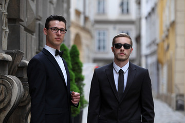 Two handsome young men in black suits standing together on the street