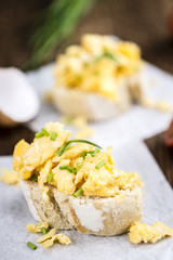 Fresh baked Bun with Scrambled Eggs on wooden background