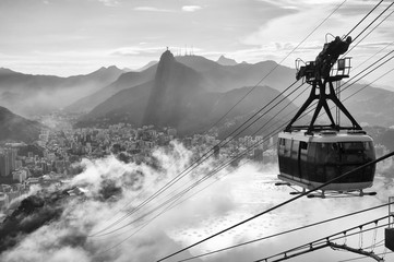 Black and white view of the misty city skyline of Rio de Janeiro, Brazil with a Sugarloaf (Pao de Acucar) Mountain cable car passing in the foreground