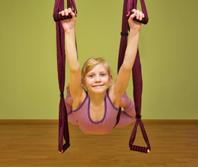 Little girl making aerial yoga exercises, indoor