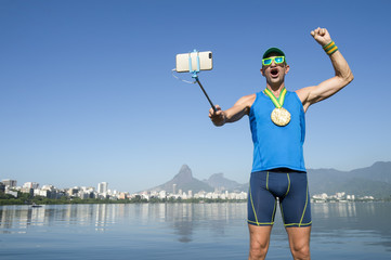 Gold medal athlete celebrating in a photo with his mobile phone on a selfie stick at Lagoa Rodrigo de Freitas Lagoon in Rio de Janeiro, Brazil