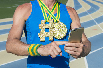 Hashtag gold medal athlete using his mobile phone standing outdoors on a blue and tan running track