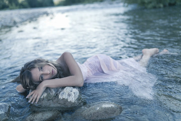 young girl model with long dress pink wet in river