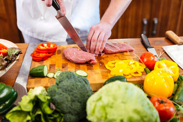 Chef cook cutting and preparing meat with fresh vegetables