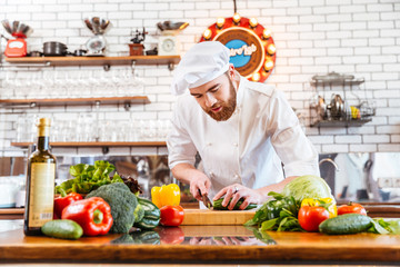 Concentrated chef cook standing and cutting fresh vegetables