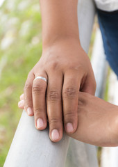 Male and female hands touching with wedding ring