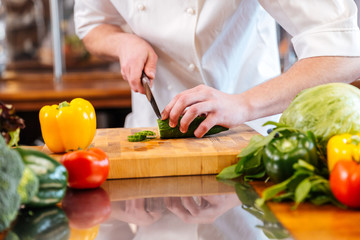 Green fresh cucumber cut by hands of professional chef cook