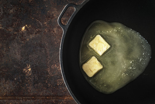 Pieces of butter in the hot pan top view
