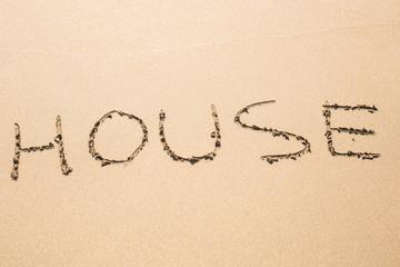 word house written in sand on beach