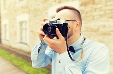 close up of hipster man with film camera in city