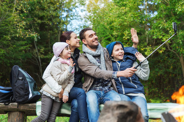 family with smartphone taking selfie near campfire