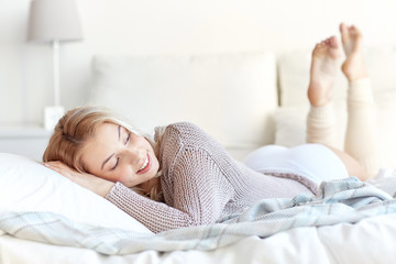 Fototapete - happy young woman lying in bed at home