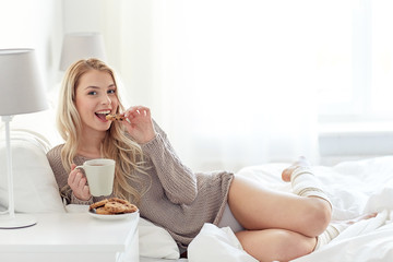 happy woman with coffee and cookies in bed at home