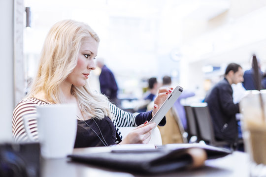 Young woman in cafe using digital tablet